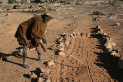 The Dogon diviner inspects and interprets fox tracks across the designs he made in the sand the night before