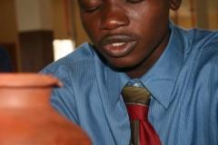 A future guardian of peace prays into the earth treasure vase in Liberia